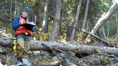 A Resource Engineering staff member surveying forest land